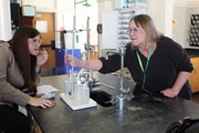 Science Department Chair Susan Park works with a student to find the molar volume of a gas.