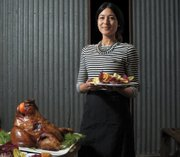 Melissa Bishop with a salad of Chinese pickles, alongside a roasted pig head.