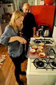 Guest Karen Pelland, features producer at KDB-FM, gets instruction from Chef Danny Douglas on how to use the torch to caramelize the sugar atop crème brûlée.