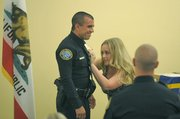 Officer Flores gets his new badge pinned by his wife.