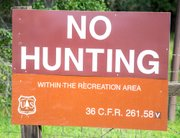 Large sign near lower Snyder Trail notes prohibition against hunting in the recreation area.