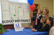 Guests at Mock City receive financial advice from volunteer Rita Lewis