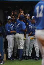 Robby Nesovic is greeted by his teammates in the dugout after doubling and scoring a run.