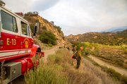 Firefighters line Paradise Road to watch for embers that might escape.
