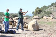 <b>BUDDIES WITH BULLETS:</b>  Cade Wilson fires a revolver while Matt Struven loads a Mosin Nagant 