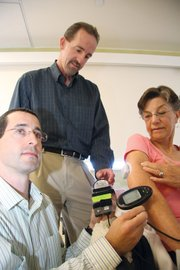 <b>Techno Treatment:</b>  UCSB's Frank Doyle (center) oversees researcher Eyal Dassau (left) analyzing data from the glucose monitor in diabetes patient Sharon Sorenson's stomach.