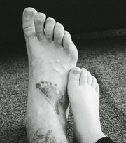 "The feet in ""Happy Feet"" belong to Staff Sergeant Evan Ahlin and his young daughter; his tat is indeed a replica of her birth footprint."