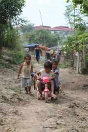 Children play on a hill in Sitio Cataquiz, a village built on an active garbage dump site just downstream from two major pharmaceutical plants.