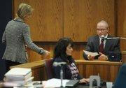 Deputy DA Paula Waldman (left) hands Det. Brian Larson a piece of evidence
