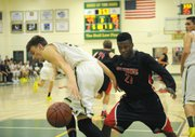 """<b>HOOP SPIRIT:</b>  This year's Holiday Classic saw Santa Barbara High and Carpinteria High go head-to-head. Pictured above, 6'5"""" Don Jack Baker (left) keeps the ball out of reach from Warrior defender Bryson Frazer (right), the fastest player on the floor."""