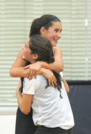 <b>FRIENDLY FOES:</b> Claire Early (left) of the Lynx hugged it out with opponent Morgan Jensen-Magne of the Stars when they accidentally collided while playing a hotly contested basketball game at the Page Youth Center.