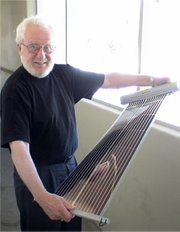 Dr. Alan Heeger holds a flexible plastic solar cell made with a roll-to-roll printing tool.