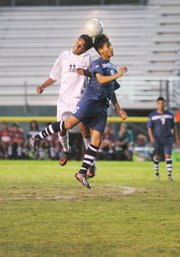 <b>HEAD-TO-HEAD:</b> Brandon Sanchez (11) of the Dons went up for the ball with Newport Harbor's David Mondragon (6) at Peabody Stadium on Thursday in the opening round of the CIF Southern Section Division 1 soccer play-offs.