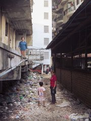 The main entrance into the community laden with trash, facing out to the newly constructed apartment complexes.