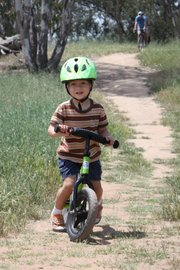 The author's 2-year-old rides the dirt trails of Lake Los Carneros with his dad.
