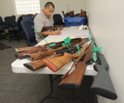 Police work to categorize and catalogue the collected guns