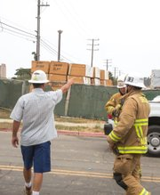 Unidentified construction company representative points out surveillance cameras to fire fighters.