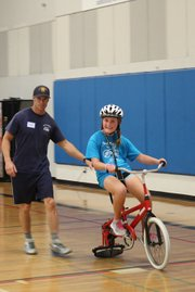 Liesl Kjoller rides with assistance from a bike camp volunteer and a roller on her bike.