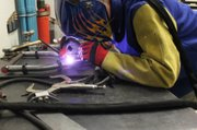 Mini Baja team member Kyle Wollert welds parts of the suspension together.