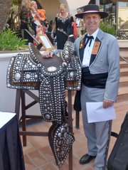 "<b>RIDING TALL:</b>  This year's El Presidente, Dennis Rickard, poses with the saddle his grandfather, James Rickard, had made in the 1920s by renowned saddle maker Luis Ortega and master silversmith John Field. Dennis's father, John ""Jack"" Rickard, also used this saddle when he rode in the Fiesta Parade as El Presidente in 1948-49."