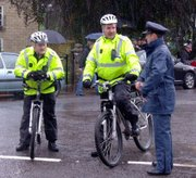 Bicycle patrol officers in the pouring rain — Pitlochry, Scotland.
