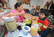 Maria Lopez (left) makes a smoothie with Storyteller Children's Center students. She says the kids will then bring donated fruit and good eating habits back home to their parents