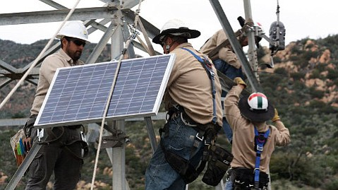 The R2-D2-shaped Flamesniffer being installed by SoCal Edison personnel on a electricity tower.