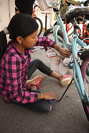 An Adams student works after school to clean and repair her bike.