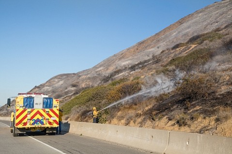 Firefighter putting out a hot spot along Highway 101 on Saturday, December 26.