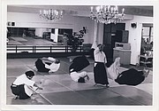 Sensei demonstrates a throw with the help of four black belts under the famous chandelier.