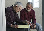 Scott Fina (left) and Dennis Apel take notes during an interview of a farm worker at the Beatitude House in Guadalupe, CA. (May 15, 2015) .