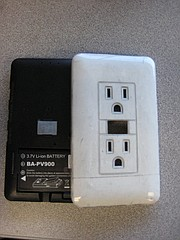 The hidden camera (left) and its electrical outlet-style casing.