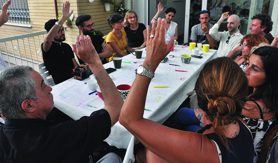 Participants in Rimini Protokoll's Home Visit USA answer questions and face challenges in a party game designed to raise awareness about issues of civil society in an age of increasing nationalism.