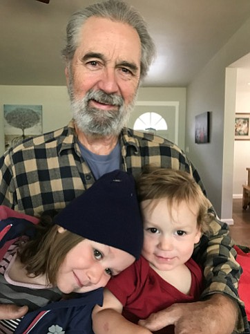 THIS IS WHY:  Author Allen DeForrest holds his grandchildren, whom he calls his personal motivators to reduce the severity of the climate change the next generations will face.