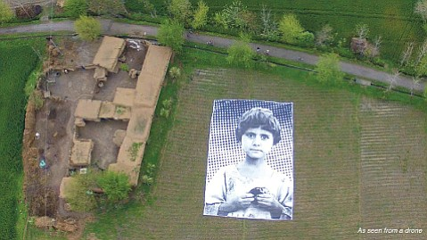 """HUMANITY BELOW:  Artist collaborative #NotABugSplat created an enormous poster to show drone operators who they were bombing. The parents of the girl photographed were killed in a drone strike, members of the """"bug splat,"""" which is military jargon for anticipated civilian casualties."""