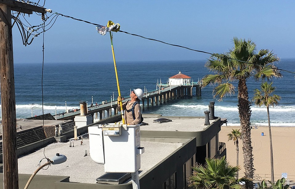 SCE troubleman Bojan Plavsic uses a hot stick to remove a metallic balloon from a power line recently in Manhattan Beach.
