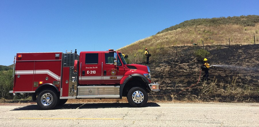 Fire crews clean up after a vegetation fire on the 7000 block of Highway 1.