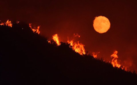 A full moon rose over flames fanning Alamo Fire on a hilltop off Highway 166 east of Santa Maria Friday night. The fire jumped a retardant line Friday afternoon and by Saturday morning had engulfed nearly 6,000 acres.