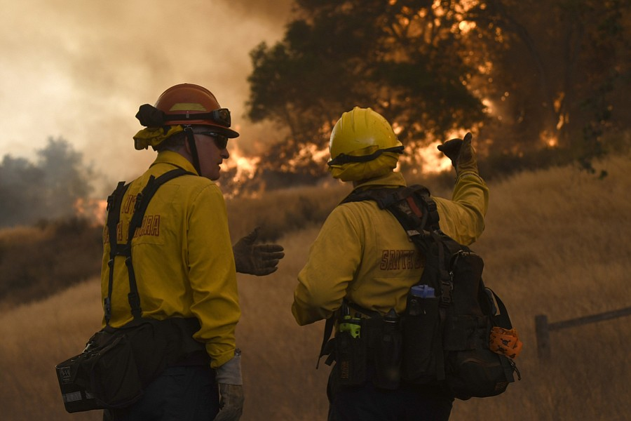 Firefighters assess their approach to the Whittier Fire as it races up oak-covered slopes alongside Highway 154.