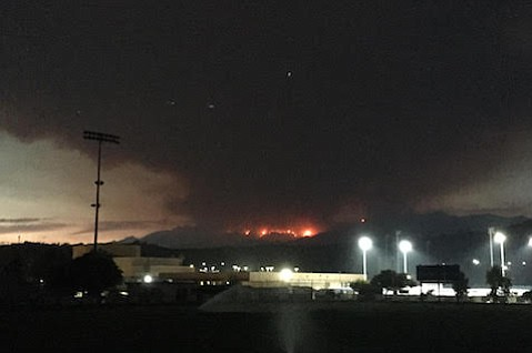 Whittier Fire burns visibly over Dos Pueblos High School late in the day.