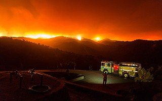 A Type 1 fire engine and its crew prepare for and await the southward march of the Whittier Fire late Friday night as the fire grew by over 3,000 acres, igniting the southern slopes of the Santa Ynez Range.