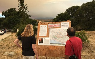 Winchester neighborhood residents check the information boards set up for the Whittier Fire.