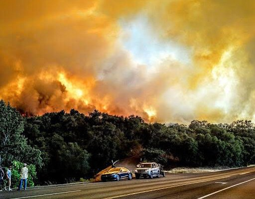 The author's friends and family await firefighters on State Route 154, the air filled with smoke and the fire burning behind them, appearing frightfully close.