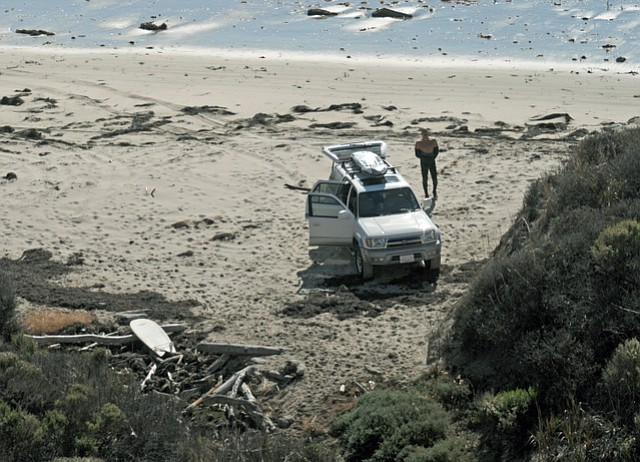A lone surfer slips out of his wetsuit after driving along to coast to access an otherwise-inaccessible beach below Hollister Ranch. Surfers and other outdoor-lovers are known to bike, drive, and walk along the coast to these remote spots.