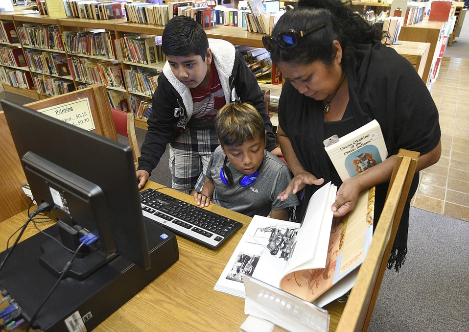 Martha Cruz (right) shows her son Anthony Gallegos (center, age 11) and his friend Diego Sandoval (left, age 10) some selected books at the Goleta Library.
