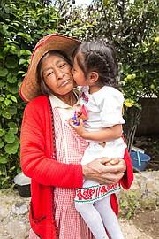 Brigida de la Cruz Mendez gets a kiss from granddaughter Esmerelda Gonzales Mendez.