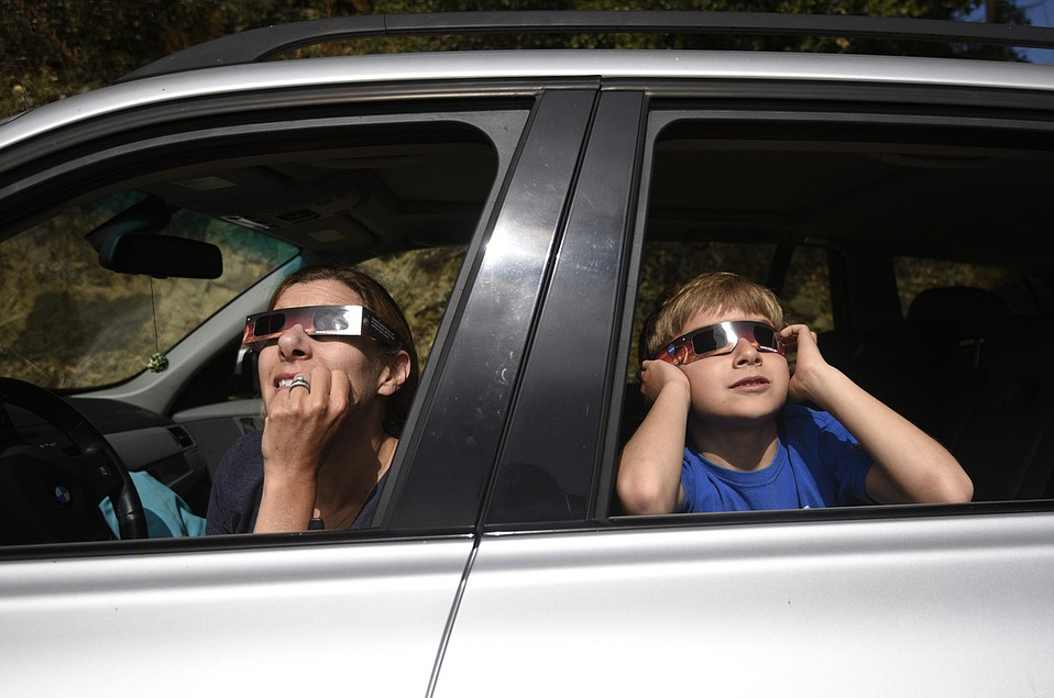 """Darian Bleecher and her son Felix watch the partial solar eclipse as seen from Stagecoach Road. Even with the glasses, Felix says, """"It's really bright."""""""