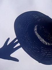 The crescent shape of the partially eclipsed sun projected through the holes of a straw hat