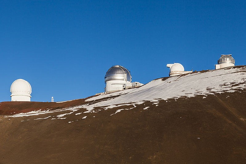 Construction of the largest telescope yet — the Thirty Meter Telescope — was recently approved for Mauna Kea, which is dotted with 13 telescopes already; shown are several at 13,780 feet.